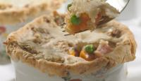 Ham and Sweet Potato Pot Pie recipe in a white and floral dish being served with a fork