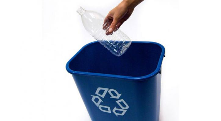 Hand placing plastic bottle into blue recycling bin