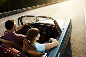 Couple taking a road trip in a vintage convertible.