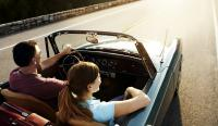 Couple taking a road trip in a vintage convertible