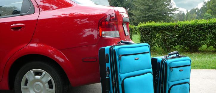 Blue suitcases against a red car