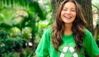 Smiling girl in green shirt with recycle symbol