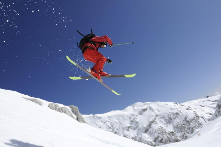 Person in red suit skiing
