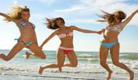 Three girls jumping on the beach in swimsuits
