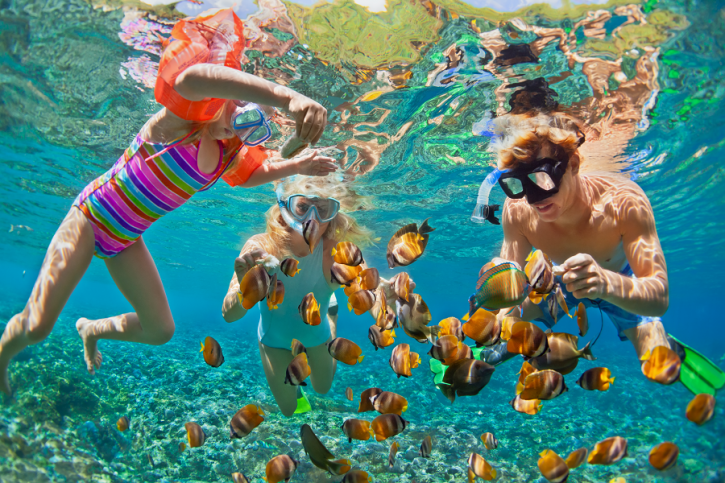 family snorkeling with tropical fish