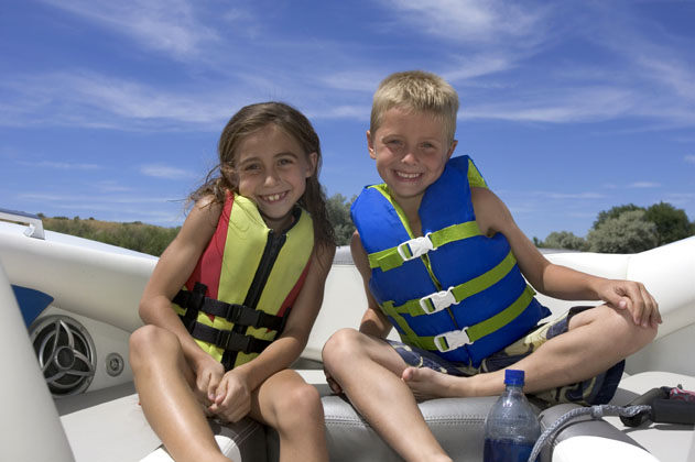 Two young children wearing life vests