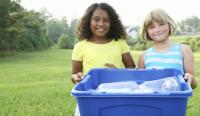 Two young children holding recycling bin