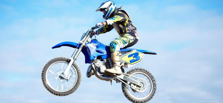 Motocross rider jumping while riding a motorcycle