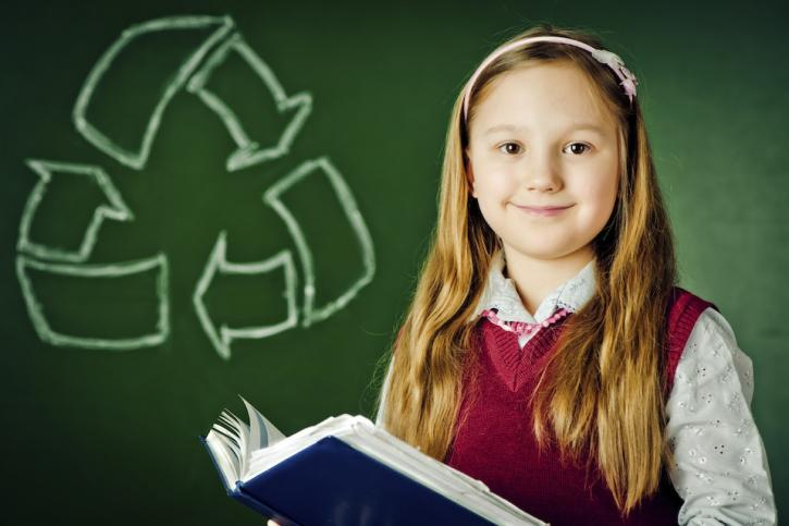 Young girl student with book in front of recycle symbol
