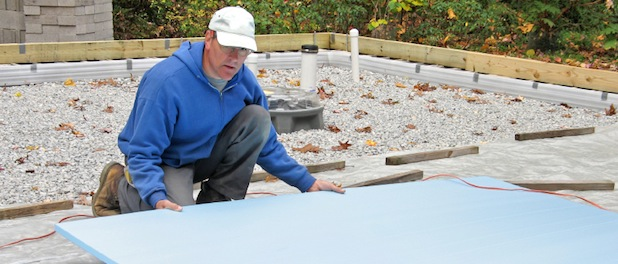 Construction worker placing plastic foam insulation on a roof