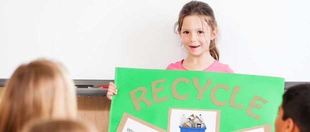 Young girl holding recycling poster