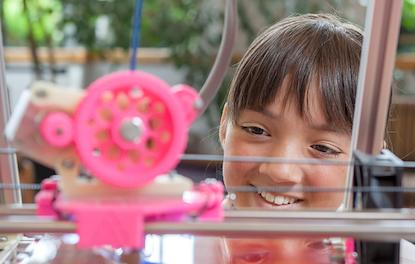 A young girl watches as a 3D printer prints an object