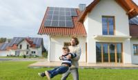Father and son in front of house with solar panels