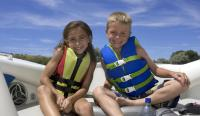 Boy and girl in life vests on a boat in summer