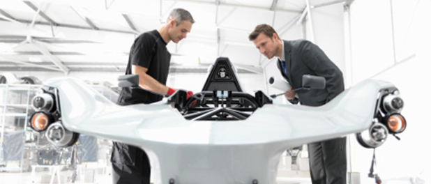 Engineer and automotive designer inspecting part-built supercar in car factory