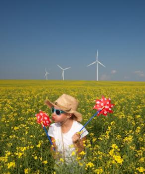 Girl in field with windmills in the background
