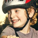 Boy riding a bike with a safety plastic helmet.
