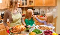 Mother cooking Thanksgiving meal in kitchen with two daughters