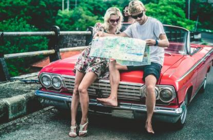 Man and woman looking at road map on car