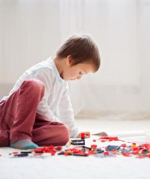 Little child playing with lots of colorful plastic blocks indoor, building a fire truck and a fire house