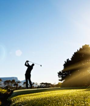 A young male golfer is silhouetted as he swings against a background of blue sky and sunshine