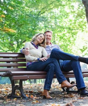 Couple sitting on recycled plastic lumber park bench