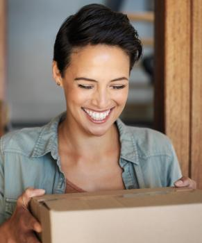 A smiling woman standing at her front door receiving a package from a courier