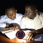 Two boys studying in the dark near a solar light