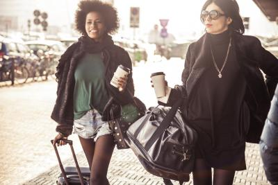 Two fashionable women walking out of the airport with luggages and coffee cup calling a taxi