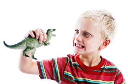 Young boy playing with dinosaur toy