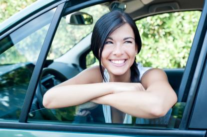 Woman sitting in car smiling