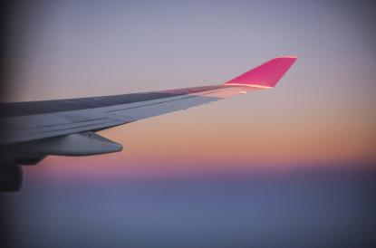 Wing of a Boeing 777-400ER over an ocean at sunrise