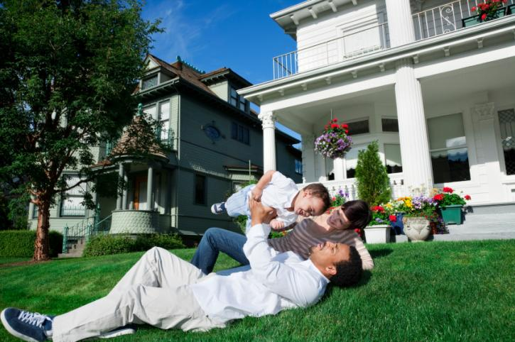 Couple laying on grass holding newborn