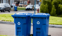 Two blue recycling bins waiting on curb for pick-up