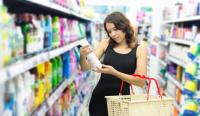 A female shopper inspects a plastic bottle of cleaner