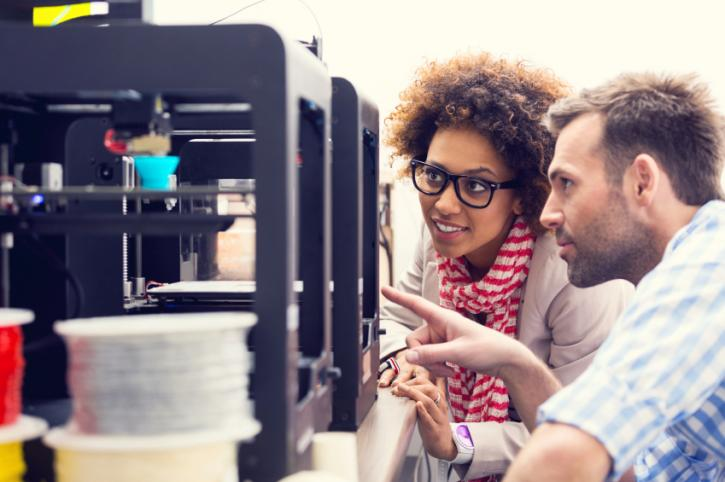 Man and woman looking at 3D printer