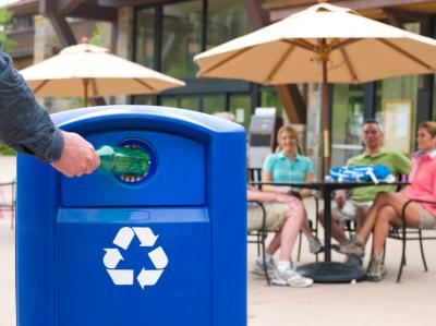 Placing a bottle into a recycling bin