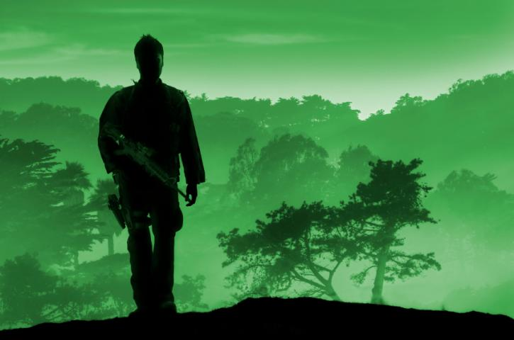 Silhouette of soldier against green forest background