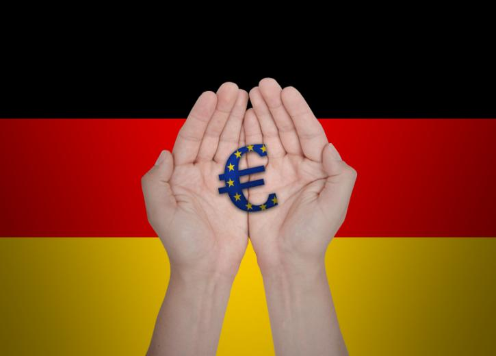 Hands holding a Euro symbol in front of German flag