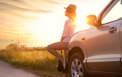 Women with parked car on the side of a country road at sunset