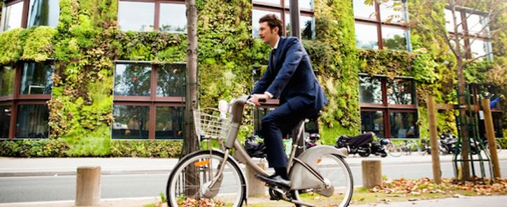 Man riding bike alongside building with living walls