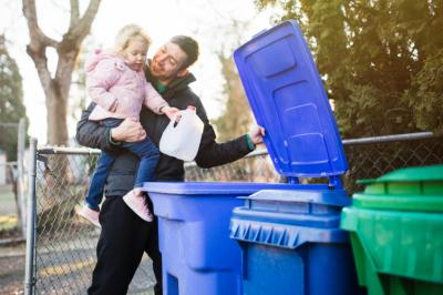 Man holding daughter while recycling