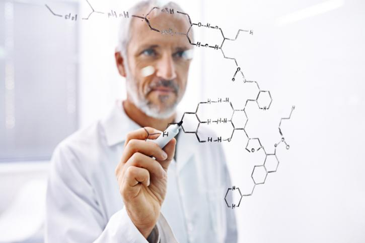 Shot of a mature male scientist drawing molecule structures on a glass surface
