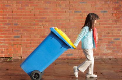 Child pulling a large recycling bin