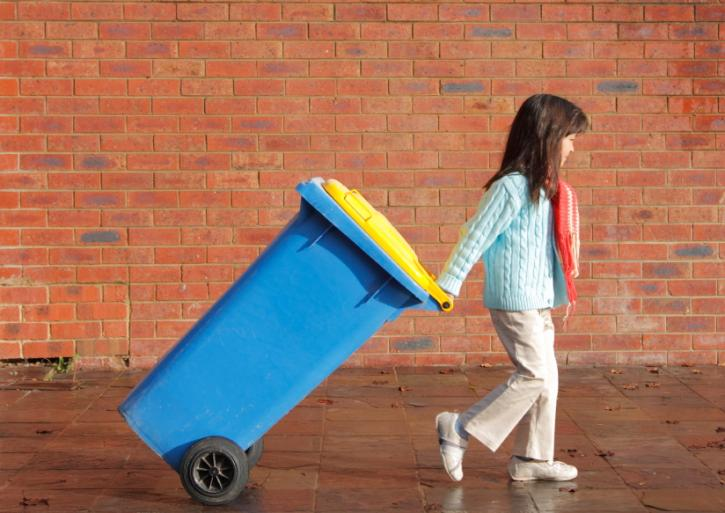 Child pulling recycling bin
