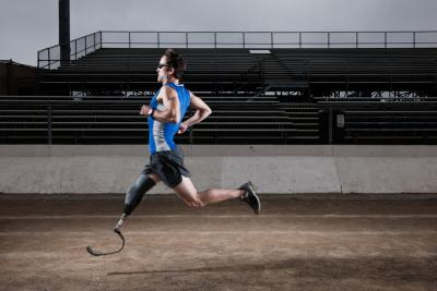 An athlete with a prosthetic leg running on the track.
