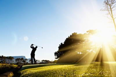 A young male golfer is silhouetted as he swings against a background of blue sky and sunshine. Copy space on clear blue sky.