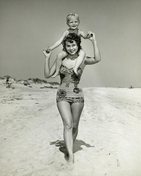 Mother carrying son (2-3) on shoulders, walking on beach, (B&W), portrait