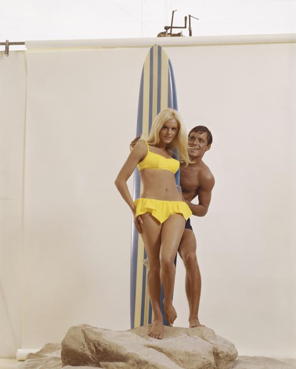 Man holding surfboard behind woman