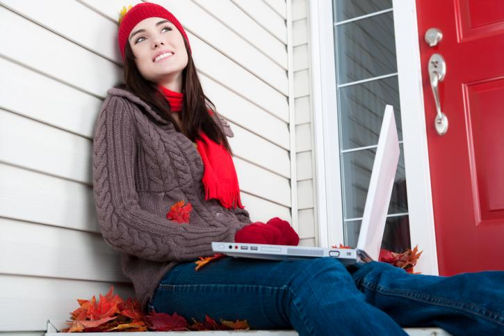 Woman on a laptop sitting on the front porch